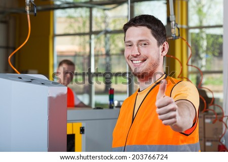 Machine operator in protective vest showing thumbs up sign - stock photo