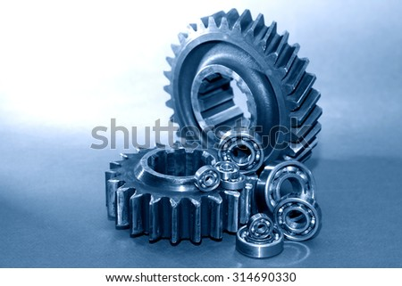 Machinery concept. Old rusty gears and ball bearing on gray background - stock photo