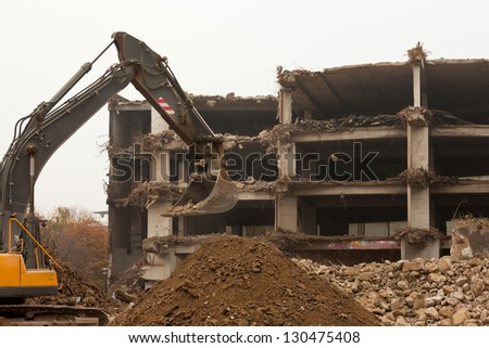 Machinery equipment working on demolition of obsolete concrete building with broken down structures - stock photo