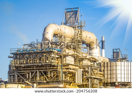 Machinery in Oil refinery plant with blue sky background.