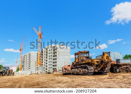 Machinery on construction site beneath blue cloudy sky - stock photo