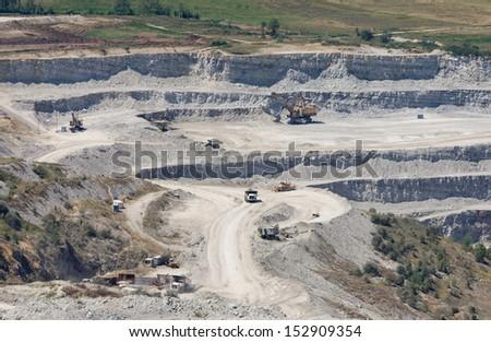 Machines working in huge quarry - stock photo
