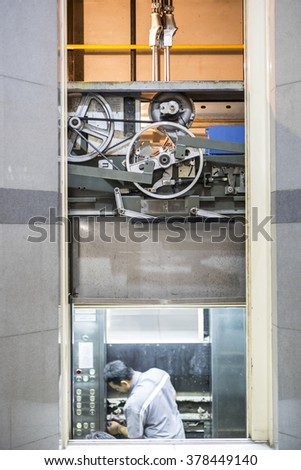 machinist worker technicians at work adjusting lift with spanners in elevator hoist way
