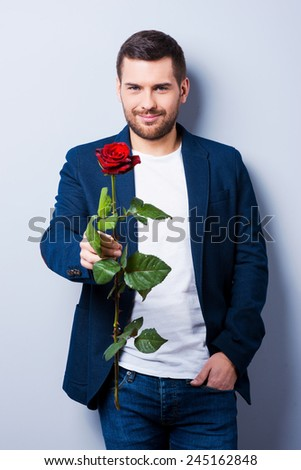 Macho and rose. Handsome young man giving a flower to you while standing against grey background - stock photo