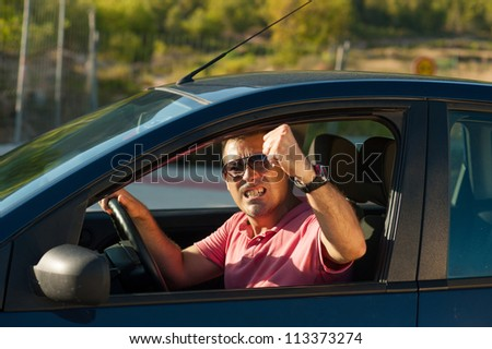 Macho driver sticking his fist out of the window - stock photo