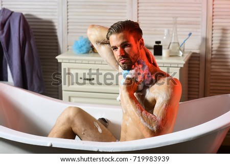 Macho Sitting Naked In Bathtub Washing With Sponge, Selective Focus. Man  With Beard And