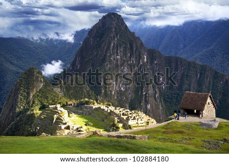 Machu Picchu at dawn with city buildings lighted by early sunrise, Peru