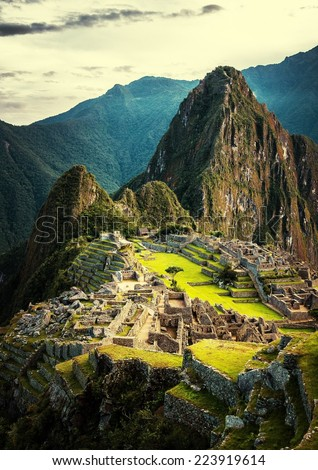 Machu Picchu at sunset when the sunlight makes everything golden-warm. Sunset at Machu Picchu, Peru. Mountain of Huayna Picchu rising above Incan ruins of Machu Picchu - Sacred Valley. - stock photo