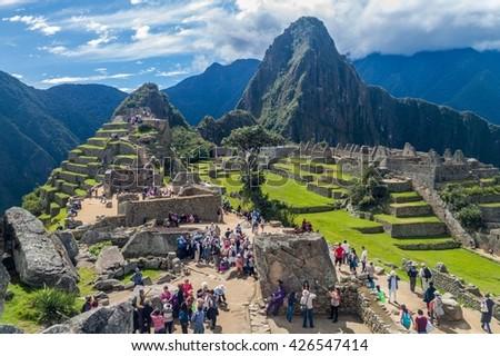 MACHU PICCHU, PERU - MAY 18, 2015: Crowds of visitors at Machu Picchu ruins, Peru. - stock photo