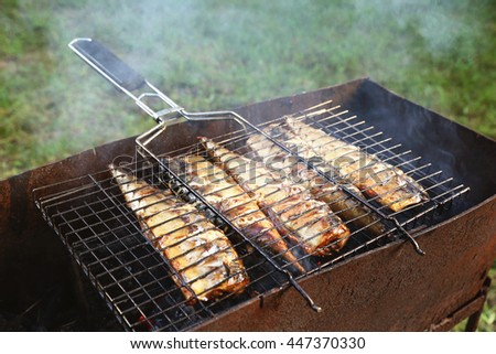 Mackerel, cooked on the grill in the open air flow. Five fishes on the grill in the smoke, tasty and fresh food, picnic, party, outdoor recreation. Grilled fish dish. - stock photo