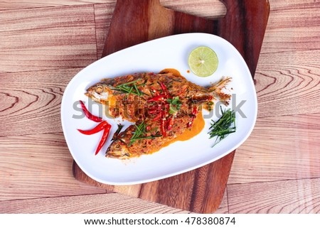 Mackerel fish fried topped spicy curry  on wood