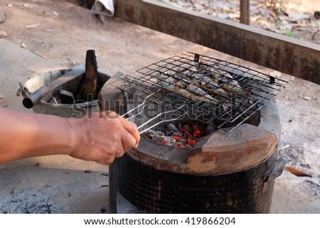 Mackerel fish on grill and hot coals - stock photo