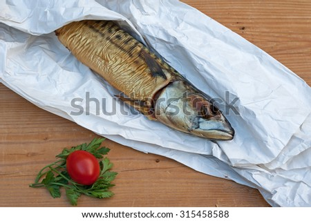 Mackerel wrapped in paper on wooden table - stock photo