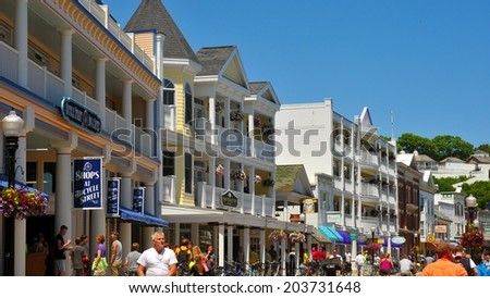 MACKINAC ISLAND, MI - JUNE 26, 2014: Main Street on Mackinac Island is thronged with tourists on a bright summer day. Fort Mackinac is visible at upper right. - stock photo