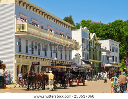 MACKINAC ISLAND, MI - JUNE 26, 2014: Main Street on Mackinac Island is thronged with tourists on a bright summer day and is the point of embarkation for many of the island carriage tours. - stock photo