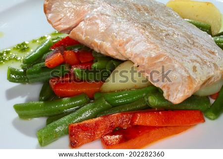 macro appetizing piece of fish on a bed of vegetables and green beans on a white plate in a restaurant - stock photo