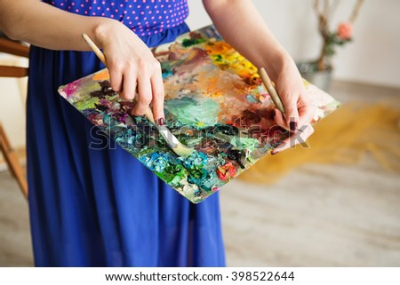 macro artist's palette, texture mixed oil paints in different colors and saturation. palette with paintbrush and palette-knife in artist??s hands. The girl artist holding a palette with oil paints - stock photo