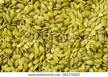 Macro background texture of green pumpkin seeds - stock photo