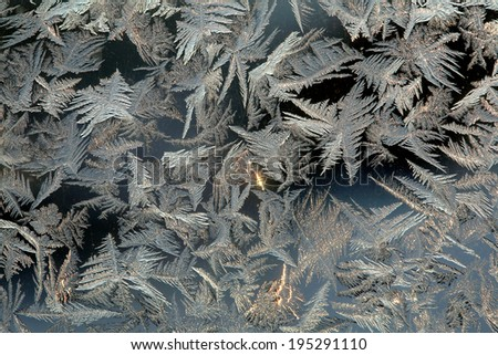 macro beautiful intricate patterns of frost on the glass in a cold winter day - stock photo