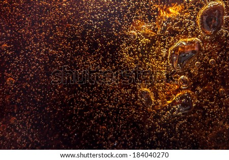Macro black bubbles on the glass wall of cola - stock photo