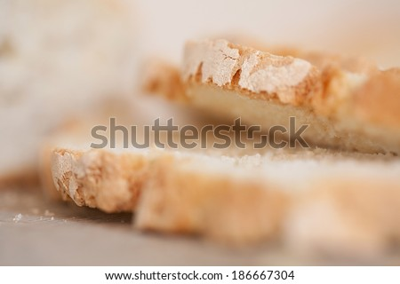 Macro close up detail of a home baked loaf of white bread with crunchy crust cut in slices with a golden color. Fresh food baking and cooking in home kitchen interior, object. - stock photo