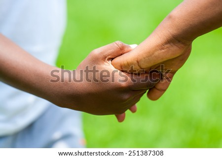Macro close up Detail of African boy holding girls hand against green outdoor background. - stock photo