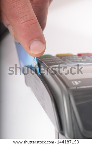 Macro / close up image of a credit card being swiped through a card machine. Focus is on the finger and front edge of the credit card