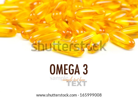 Macro close up of a pile of Omega 3 fish oil capsules with sample text. Focus in center of image and front of pile. Shot in studio on a white background. - stock photo