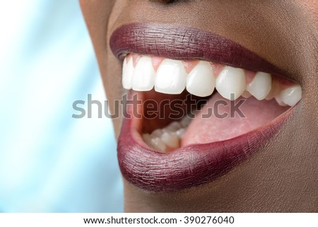 Macro close up of african female mouth.Open mouth showing perfect white teeth.  - stock photo