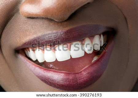 Macro close up of african female mouth showing perfect white teeth.