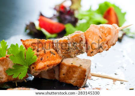 Macro close up of appetizing char broiled salmon and tuna skewer seasoned with herbs. - stock photo