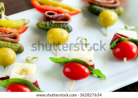Macro close up of assortment of mini finger food appetizers. Variety of small skewers on white plate. - stock photo
