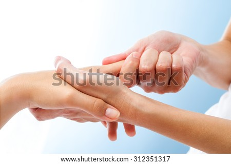 Macro close up of curative hand massage. Therapist manipulating female hand.