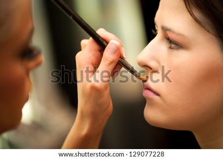 Macro close up of female hand painting face at make up session. - stock photo