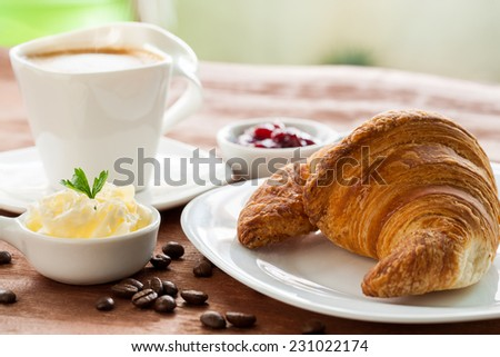 Macro close up of fresh croissant with hot coffee in background. - stock photo