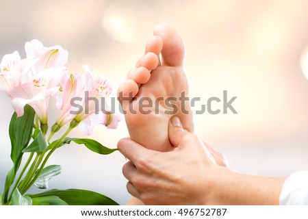 Macro close up of hands applying pressure on female foot.