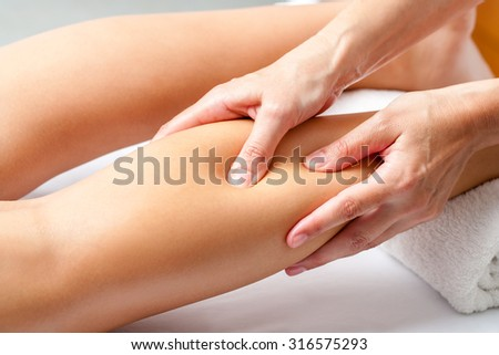 Macro close up of Hands applying pressure with fingers on calf muscle. Osteopath doing healing massage on female leg.