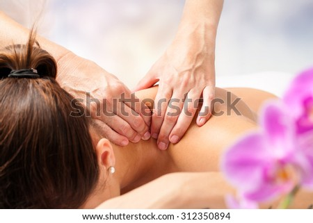 Macro close up of hands massaging female neck and shoulders. - stock photo