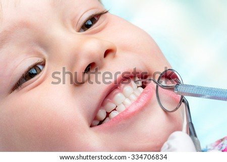 Macro close up of little life year old showing teeth at dental check up.Dentist hands holding mouth mirror and hatchet near teeth.