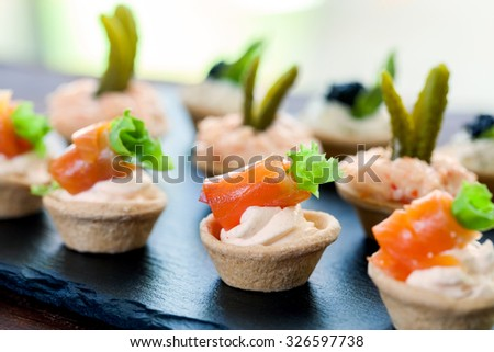 Macro close up of Mini puff pastry tart lets with smoked salmon,creamy crab and savory filling.