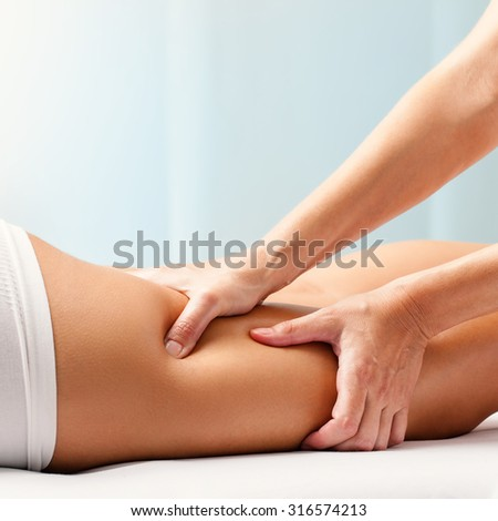 Macro close up of Osteopathic hamstring massage.Therapist applying pressure with hands on back go female leg.