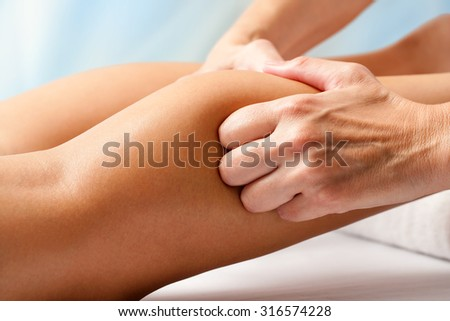 Macro close up of Physiotherapist hands massaging female calf muscle. - stock photo