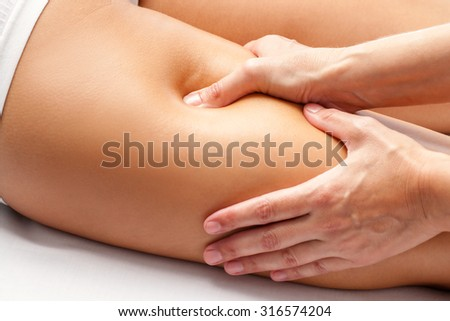 Macro close up of Physiotherapist hands massaging hamstring on female athlete.