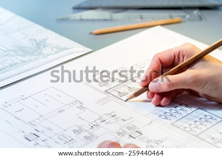 Macro close up of quantity surveyors hand reviewing technical drawing. - stock photo