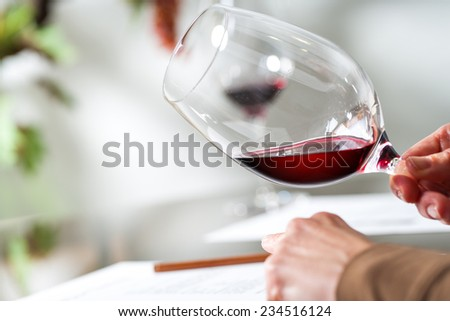 Macro close up of Sommelier evaluating wine at tasting. - stock photo