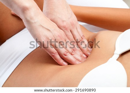 Macro close up of therapist hands doing visceral massage on female abdomen. - stock photo