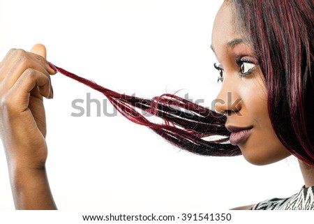Macro close up portrait of young African woman looking at dry edges of dyed hair.Isolated on white background.