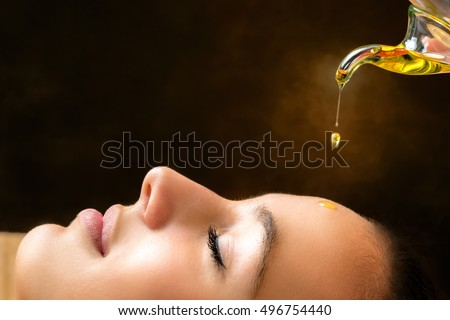 Macro close up portrait of young woman at ayurvedic massage session with aromatic oil dripping on face.