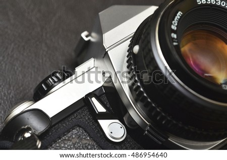 Macro close up shot of a silver classic film camera SLR with lens