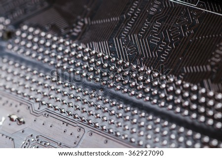 Macro closeup of a computer PCB Motherboard using brown and black colors with silver soldered terminals - stock photo